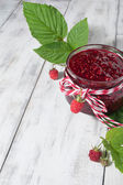 Raspberry jam in a jar on the wooden table — Stock Photo