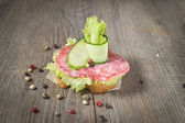 Canape with salami, cucumber and salad on wooden table — Stock Photo
