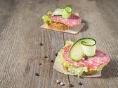 Canape se salámem, okurkou a salátem na dřevěný stůl — Stock fotografie