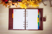 Day planner with yellow flowers on the table. — Stock Photo