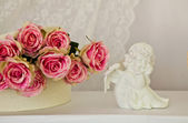 Angel statuette and roses — Stock Photo