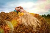 Woman lying on hay — Stock Photo
