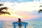 Female relaxing on a beach bench — Stock Photo