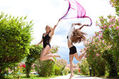 Girls jumping with pink fabric — Stock Photo