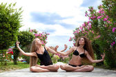 Women sitting in lotus pose — Stock Photo