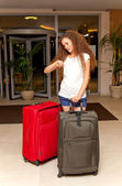 Woman with suitcases checking time — Stock Photo