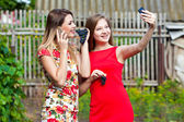 Girls making selfie and eating grapes — Stock Photo