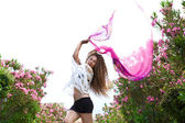 Girl jumping with pink fabric — Stock Photo