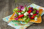 Salad greens, strawberries and blue cheese on a wooden backgroun — Stock Photo