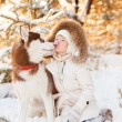 Happy Little Blonde girl is having fun with her big dog in snow — Stock Photo #47031085