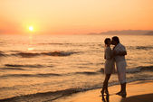 Man and woman kissing at beach with sunset in the background, It — Stock Photo
