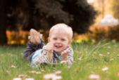 小さな男の子が、デイジー、芝生の上で遊んで公園に横たわる — ストック写真