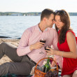 Happy young couple enjoying picnic on the beach and have good time on summer vacations — Stock Photo #47372451