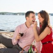 Happy young couple enjoying picnic on the beach and have good time on summer vacations — Stock Photo #47372457