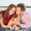 Happy young couple enjoying picnic on the beach and have good time on summer vacations — Stock Photo #47372499