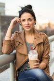 Beautiful happy girl drinking a cup of coffee - outdoor portrait — Zdjęcie stockowe