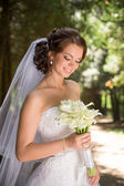 Beautiful bride in wedding dress and bridal bouquet, happy newlywed woman with wedding flowers, woman with wedding makeup and hairstyle. gorgeous young bride outdoors. Bride waiting for groom. bride — Stock Photo