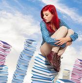 Woman sitting on books — Stock Photo