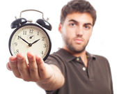 Young man holding alarm clock — Stock Photo