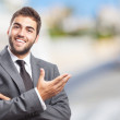 Businessman doing welcome gesture — Stock Photo #47347399