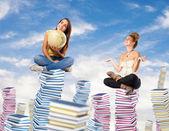 Women sitting on book piles — Stok fotoğraf
