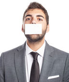 Businessman with mouth covered — Stock Photo