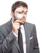 Business man looking through magnifying glass — Stock Photo