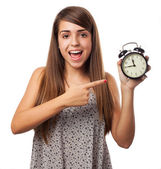 Young woman pointing at alarm clock — Stock Photo