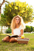 Woman reading book at park — Stock Photo