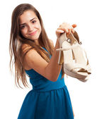 Elegant woman holding high heeled shoes — Stock Photo