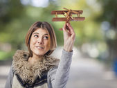 Woman playing with wooden plane — Stock Photo
