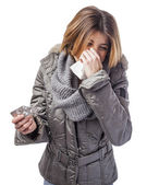 Woman sneezing and holding medicines — Stock Photo