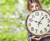 Business woman holding clock — Stock Photo