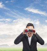 Man looking trough binoculars — Stock Photo