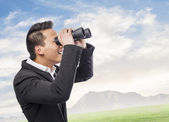 Man looking trough binoculars — Stock Photo