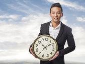 Business man holding clock — Stock Photo