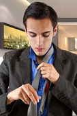 Businessman getting dressed in a hotel — Stock Photo