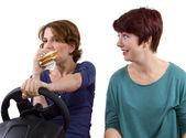 Controlador mujer comiendo un sándwich mientras que conduce — Foto de Stock