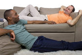 Two gay lovers relaxing in the livingroom — Stock Photo