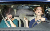 Woman smoking while driving inside the car — Stock Photo