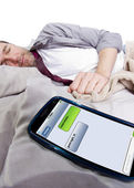 Cell phone screen showing text messages while male is in bed — Stockfoto