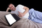 Male reading on a tablet before going to sleep — Stock Photo