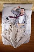 Бизнесмен, спать с сотовый телефон будильник — Стоковое фото