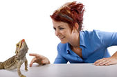 Girl staring at spikey bearded dragon reptile — Stock Photo