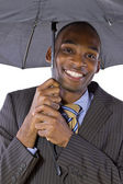 Black businessman under umbrella — Stock Photo