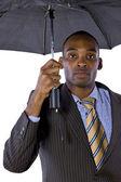 Black businessman under umbrella — Stock Photo
