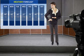 Woman on stage with weather chart and camera — Stock Photo