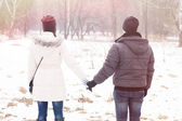 Couple holding hands in the winter park — Stock Photo