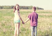 мальчик держит руку девушки на зеленом поле — Стоковое фото