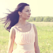 Woman in pink dress  in a field — Stock Photo